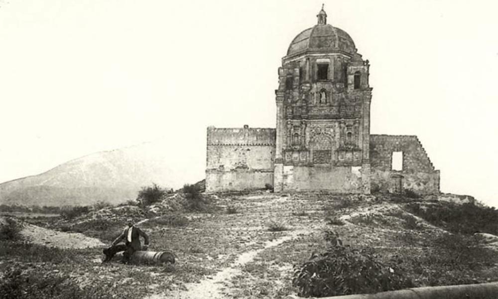 persona posando con el palacio del obispado en sus primeros años